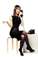 Happy young fashion woman calling on retro phone