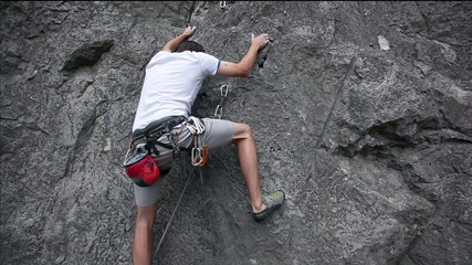 Young man rock climbing in nature