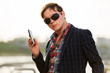 Young fashion man in sunglasses with a mobile phone outdoor