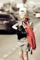 Young fashion woman with handbag walking on a city street