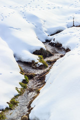 Small river flowing between two hills in winter time