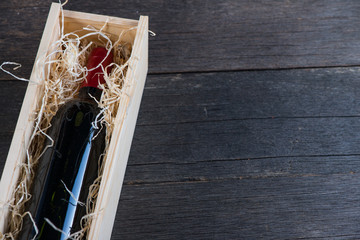 Red wine bottle in wooden case with straw on rustic background