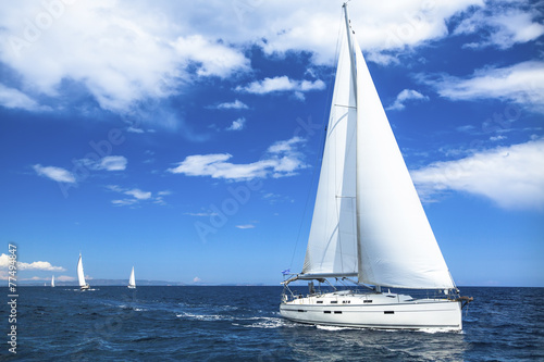 Sailing boat yacht or sail regatta race on blue water Sea. - 77494847