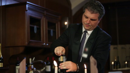 Close up shot of a waiter who is opening a bottle of old, special wine