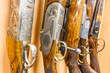 close up of a row of guns displayed in gun shop - 77496075