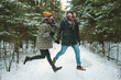 Young hipster couple jumping in winter forest - 77496226
