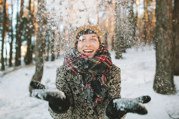 Young woman  with snow in hands in winter forest