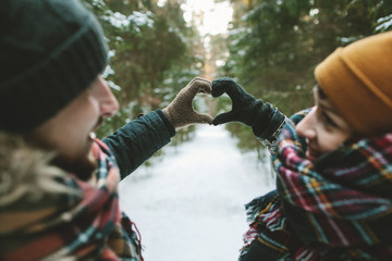 Young hipster couple holding hands in love symbol