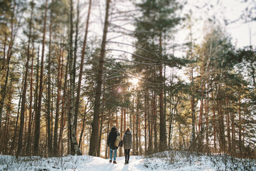 Young couple standing alone in winter forest