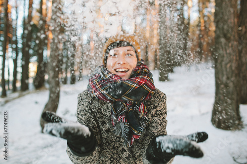 Young woman  with snow in hands in winter forest - 77496213