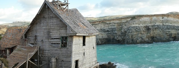 Old derelict wooden house overlooking the sea