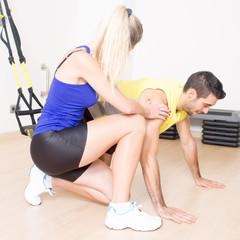 Weiblicher Trainer hilft bei Liegestützen