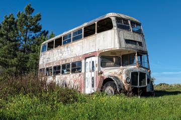 Rusty Abandoned Double-Decker Bus Standing in a Field