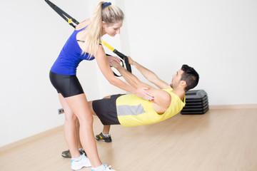 Weiblicher Trainer hilft bei Schlingentraining