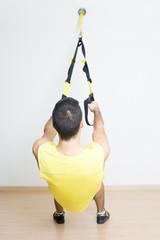Sporty man makes suspension training
