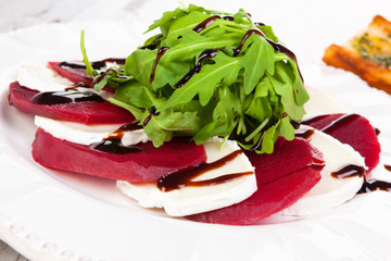 Beet with goat cheese and fresh salad close up.