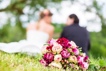 Hochzeitspaar mit Brautstrauß sitzt auf Wiese