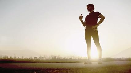 Marathon runner drinks water amidst beatiful nature