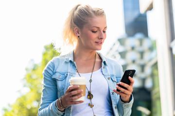 Frau mit Kaffee und Handy in Stadt