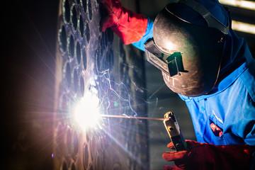 Welder working in industrial factory
