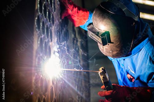 Welder working in industrial factory - 77499847