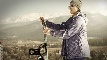 Everyday ski resort scene: attractive Girl with Snowboard
