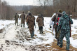 Group of hunters walking on the field in winter