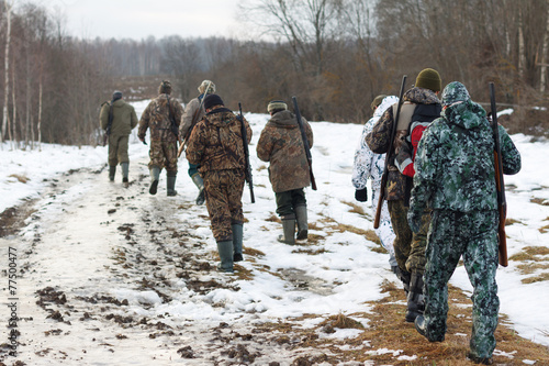 Group of hunters walking on the field in winter - 77500477