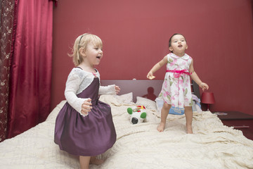 little girls jumping on a bed