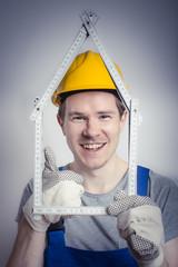 Bauarbeiter mit Zollstock in Form eines Hauses