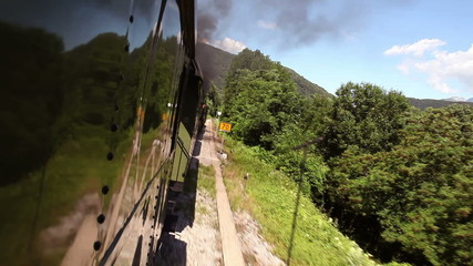 Shot of the train passing through the landscape,  with reflection of it on the carriage