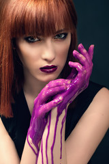 Beautiful woman with fingers covered in paint