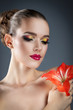 beautiful woman with bright makeup and red flower