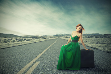 Woman sitting on suitcase on countryside road waiting for ride