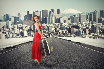 woman with suitcase baggage standing on road waiting for a ride