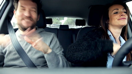 Couple in love dancing in car driving