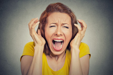 Headshot angry woman screaming hysterical grey background
