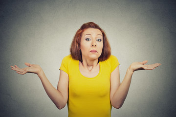 puzzled clueless woman shrugs shoulders on grey background