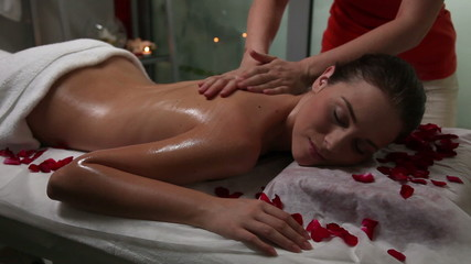 Young woman enjoying massage in a spa center
