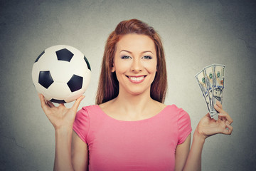 Football and money. Woman holding cash and soccer ball