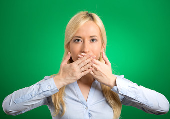 woman covering closed mouth with hands green background
