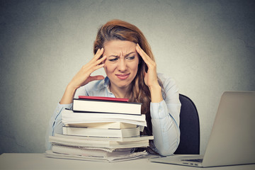 stressed woman sitting at desk with books computer