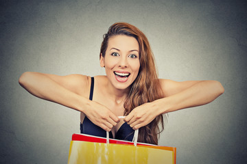 woman with many shopping bags on gray wall background
