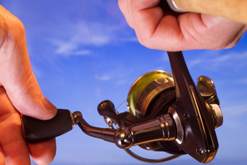 spinning reel in hand close-up against the sky