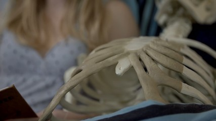 Close shot of woman reading to a skeleton
