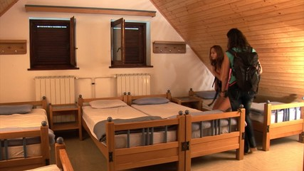 Teenagers enter their shared bedroom with their luggage