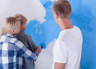 Little boy painting wall