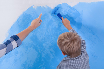 Little boy painting his room