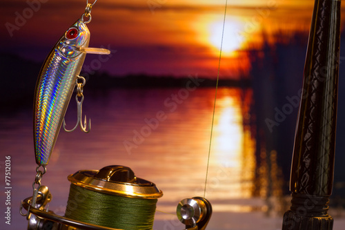 Fishing bait wobbler against the setting sun in a river - 77512036