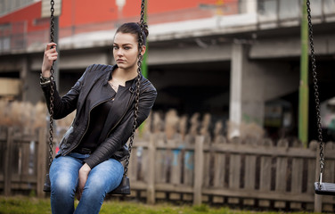 Beautiful girl sitting on a swing and looking